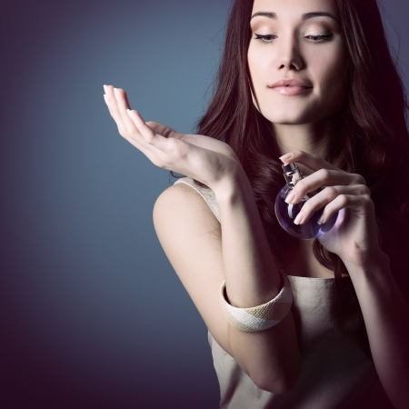 Woman with perfume, young beautiful girl holding bottle of perfume and smelling aroma, over blue purple background Stock Photo - 19930963