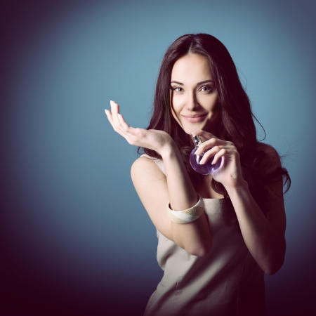 Woman with perfume, young beautiful girl holding bottle of perfume and smelling aroma, over blue purple background Stock Photo