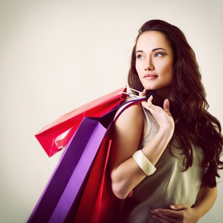 beautiful young woman holding colored shopping bags, toned photo