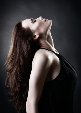 Young woman with beautiful long brown hair posing at studio, profile over black background, toned photo