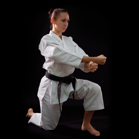 black belt: karate girl with black belt posing, champion of the world, on black background studio shot Stock Photo