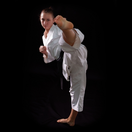 karate girl with black belt posing, champion of the world, on black background studio shot Stock Photo