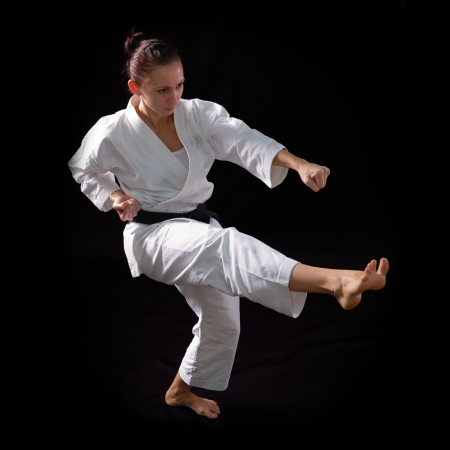 karate girl with black belt posing, champion of the world, on black background studio shot photo
