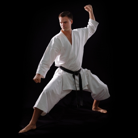 karate man with black belt posing, champion of the world on black background studio shot photo
