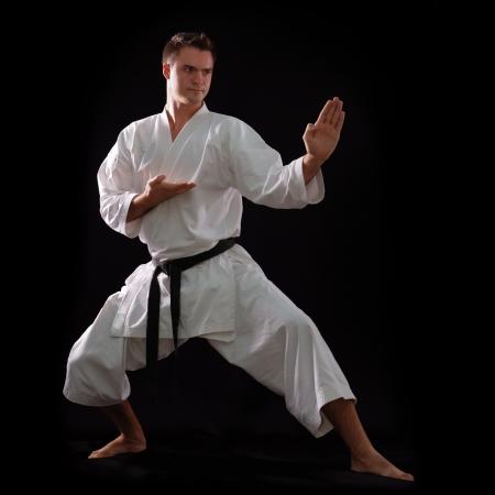 sensei: karate man with black belt posing, champion of the world on black background studio shot