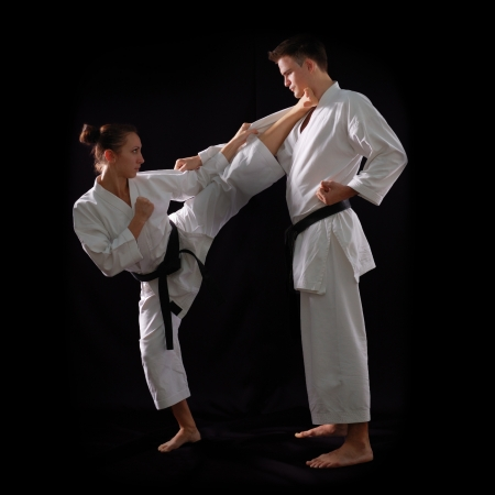 karate fighter: fighting karate couple, man and woman with black belts - champions of the world, on black background studio shot