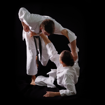 karate female: fighting karate couple, man and woman with black belts - champions of the world, on black background studio shot