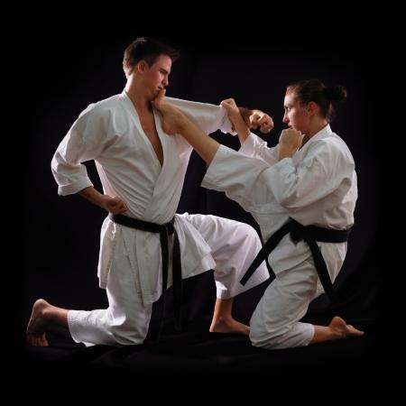 patada: Lucha de los pares karate, hombre y mujer con cinturones negros - campeones del mundo, sobre fondo negro tiro del estudio