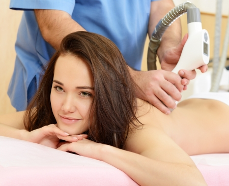 young beautiful woman getting massage therapy on back in beauty salon photo