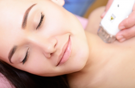 beautiful face of young woman and rejuvenated treatment, lady lies on a couch in a beauty spa getting electrostimulation lifting therapy photo