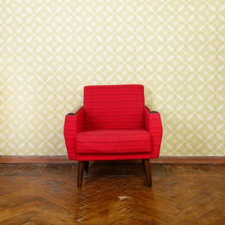 Vintage room with old fashioned red armchair, wallpaper and weathered wooden parquet floor
