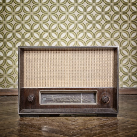 vintage radio receiver device on the weathered wooden parquet floor in vintage room with old fashioned wallpaper, toned