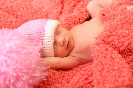 sleeping cute baby funny pink hat in soft fabric and smiling in sweet dreams, beautiful kid's face closeup photo