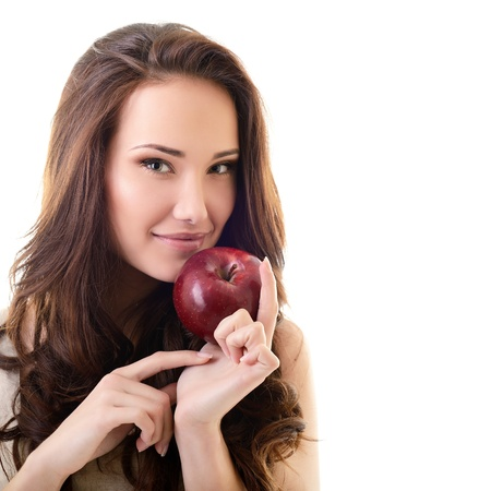 Attractive teen girl with an apple against white background  photo