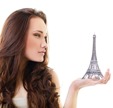 french model: Beautiful girl holding little Eiffel tower, over white Stock Photo
