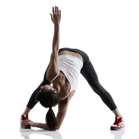 portrait of sport girl doing yoga stretching exercise, studio shot in silhouette technique over white background photo