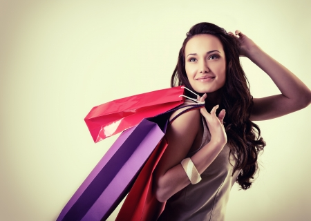 beautiful young woman holding colored shopping bags, over white, tone photo