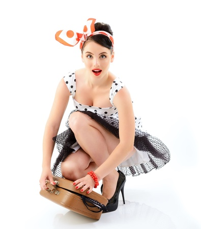 Pinup girl with suitcase in dress spotted, full length retro portrait of young happy sexy woman in pin-up style, vintage stylization over white photo
