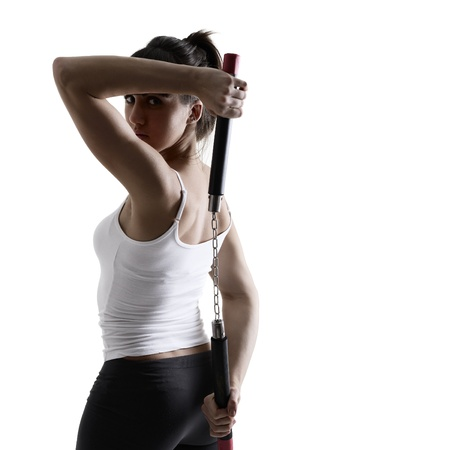 sport karate girl doing exercise with nunchaku, fitness silhouette studio shot over white background Stock Photo