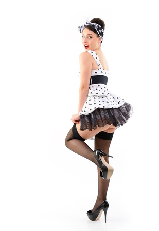 Pinup girl on high heels in spotted dress stocking, full length portrait of seductive young happy sexy woman in pin-up style, over white photo
