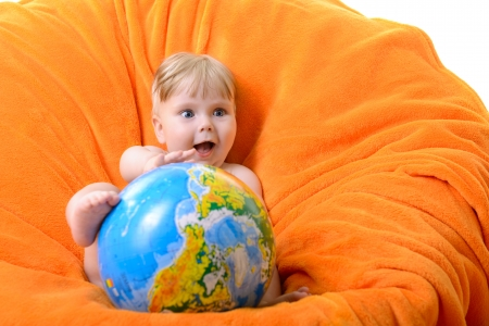Happy smiling baby boy playing with terrestrial globe sitting on an orange soft armchair photo
