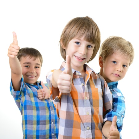 thumbs up of cute little boys friends in cheched shirts, on a white background photo