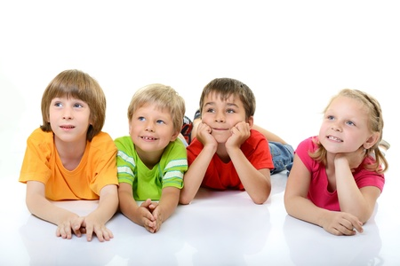 choleric: cute children in colored t-shirts lying and smiling looking with interest up in left corner, over white background