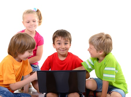 children playing together: happy children playing and learning with laptop, over white Stock Photo