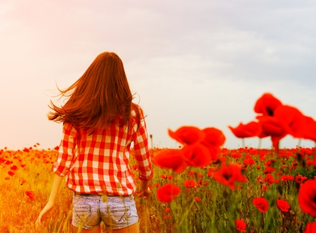 Young beautiful woman walking and dancing through a poppy field, summer outdoor. Toned. photo