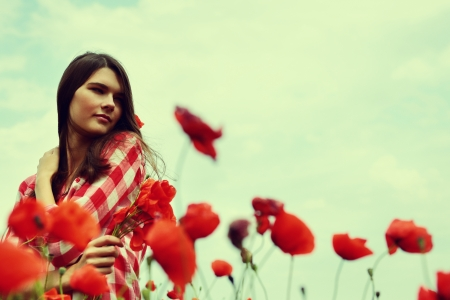 Portrait of calm beautiful girl through a poppy field, summer outdoor. Toned, noise added. photo