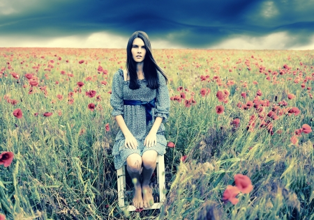 Mysterious portrait of young beautiful woman sitting on stool in a poppy field and looking at camera, summer nature outdoor. Toned. photo