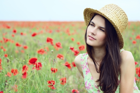 gentle dream vacation: Young beautiful calm girl in straw hat dreamomg on a poppy field, summer outdoor. Toned, noise added. Stock Photo