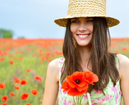 Young beautiful happy woman in straw hat on a poppy field, summer outdoor. photo