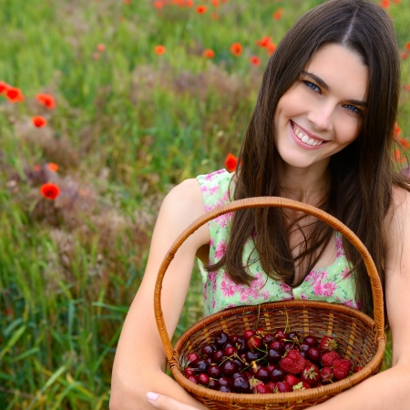 Young beautiful woman holding basket with cherry and strawberry on a poppy field, summer nature outdoor. photo