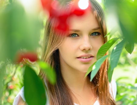 portrait of pretty cheerful young teen girl in summer cherry garden  photo