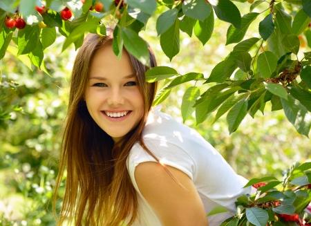 beautiful garden: portrait of pretty cheerful young girl in cherry garden