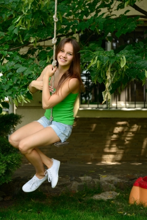 Happy teen girl on a swing, summer park outdoor photo