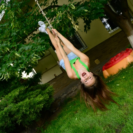 moving down: Happy excited teen girl on a swing upside down, summer park garden outdoor Stock Photo