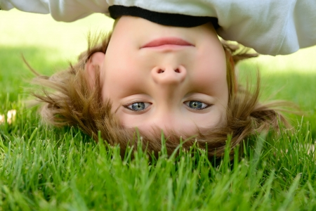 Happy little boy standing upside down on green grass in spring park. photo