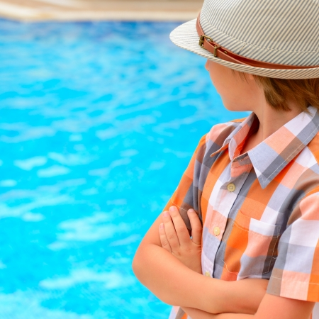 swimmingpool: Summer portrait of carefree little boy in hat outdoor near swimming-pool