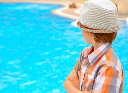 swimmingpool: Summer portrait of carefree little boy in hat outdoor near swimming-pool