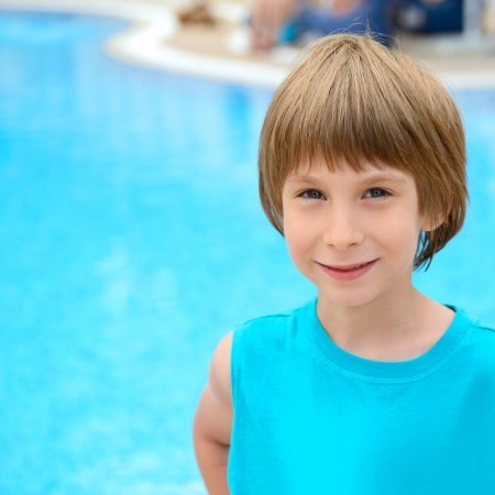 swimmingpool: Summer portrait of carefree little boy outdoor near swimming-pool
