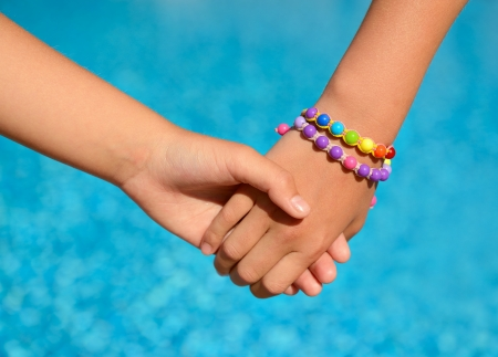 bangle: children hands over blue water outdoor, summer kids vacation concept Stock Photo