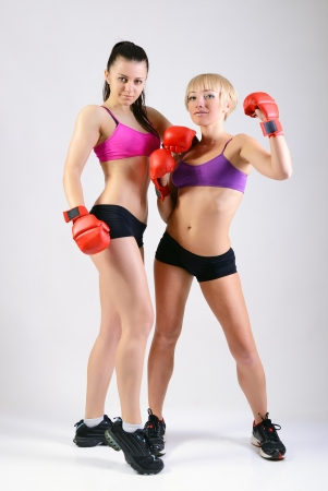 sport training of two boxing young woman, studio photo