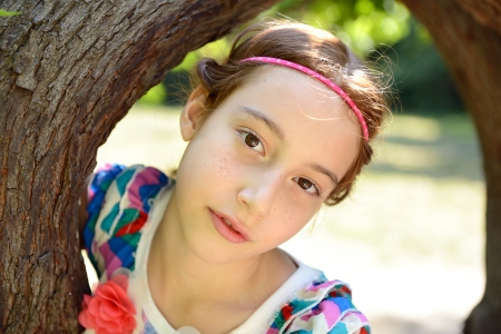 face in tree bark: girl embrace tree, smilig and looking at camera