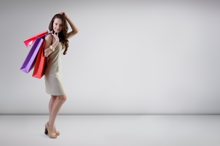 Beautiful young woman posing at studio with shopping bags, full length portrait photo