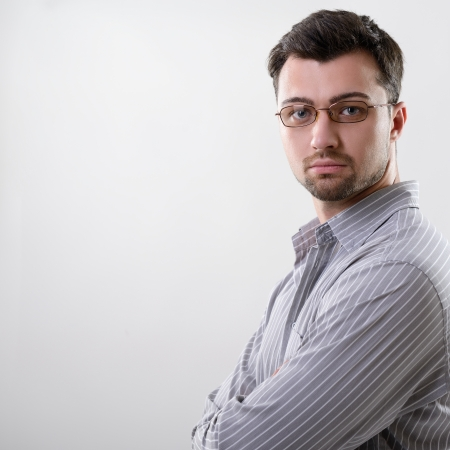 centred: Handsome concentrated young business man, studio over gray background