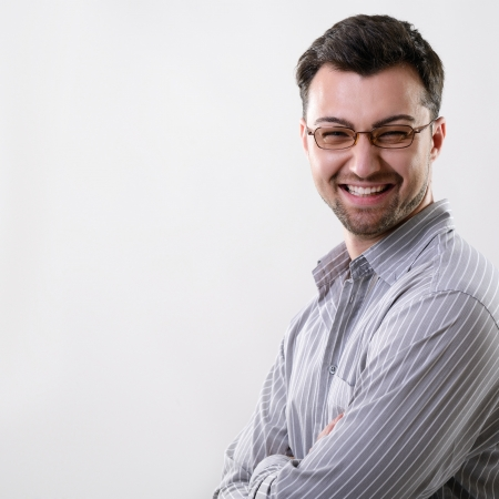 latin man: Happy smiling handsome young business man, studio over gray background