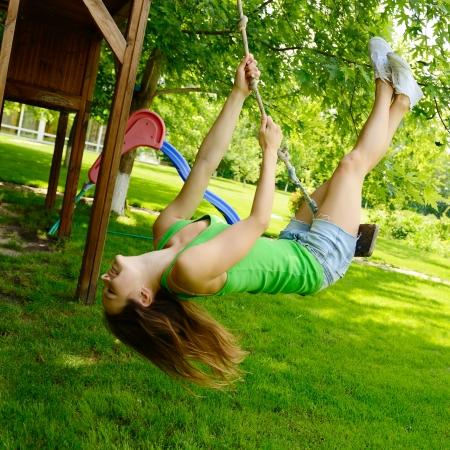 columpios: Chica adolescente feliz, emocionada en un columpio, parque de verano al aire libre