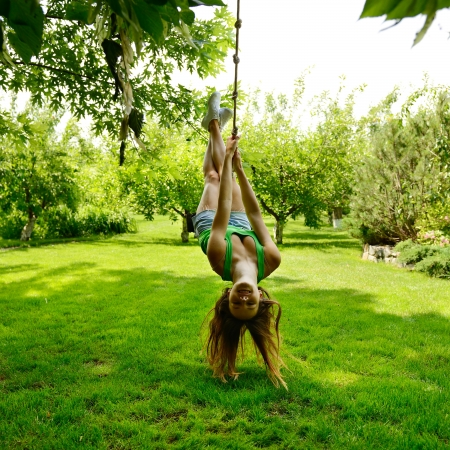 Happy excited teen girl on a rope swing, summer park outdoor photo
